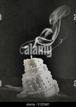 An extinguished and collapsed wedding cake candle. - Stock Photo