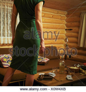 Canada, Alberta, Cochrane, Rear view of woman in mid-century styled log cabin wearing retro dress - Stock Photo