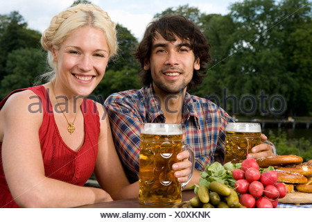 A man and a woman sitting in a beer garden - Stock Photo