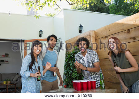 Laughing friends playing beer pong on patio - Stock Photo