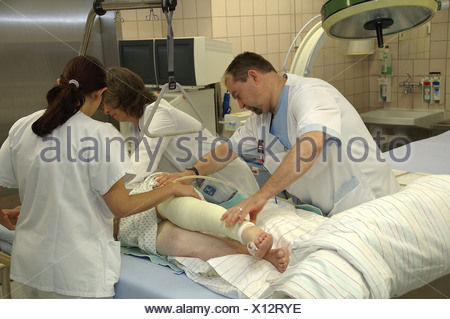 Orderly And Doctor Turn Patient With Gypsum Leg On Bed Stock Photo