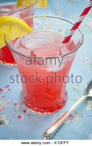 Two Glasses of a Lemon Cherry Cocktail on Blue Table Cloth - Stock Photo