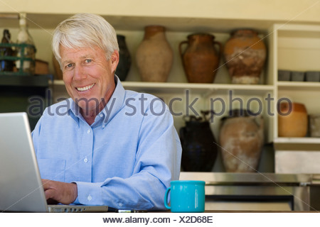 Man at laptop with mug smiling - Stock Photo