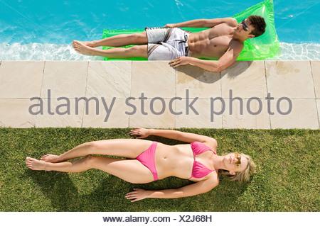 Couple sunbathing at the pool - Stock Photo