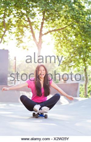 USA, Washington, Seattle, Cheerful young woman sitting on skateboard - Stock Photo