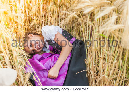 Germany, Saxony, portrait of smiling girl lying in a grain field wearing dirndl - Stock Photo