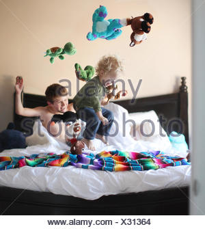 Boy jumping on brothers bed and throwing soft toys in the air - Stock Photo