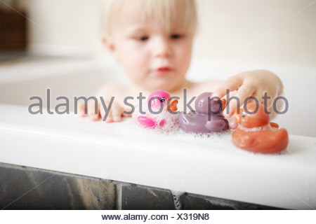 Toddler playing with toys in bath - Stock Photo
