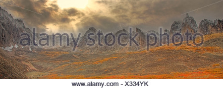 Clearing storm, sun rays poking through clouds and autumn colours in the Tombstone Valley in Tombstone Territorial Park, Yukon - Stock Photo