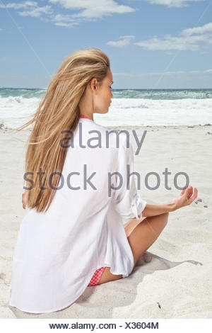 Young woman sitting in lotus position on the beach - Stock Photo