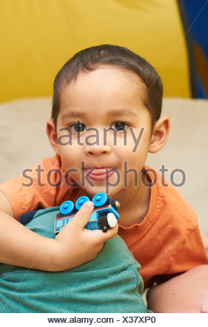 Boy playing with toy train - Stock Photo