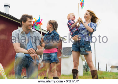Parents with children holding pinwheels - Stock Photo