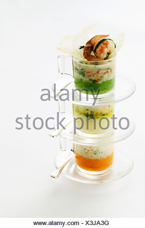 Three kinds of vegetable puree with crayfish in stacked cups - Stock Photo