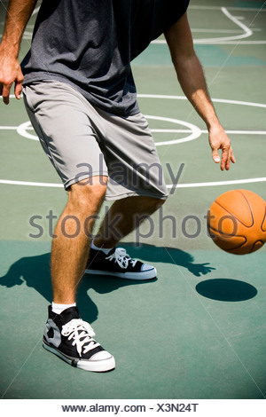 Man on an outdoor basketball court, close up - Stock Photo