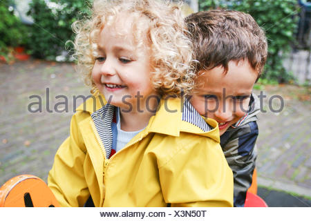 Smiling Boy and girl sitting on spring ride in playground - Stock Photo