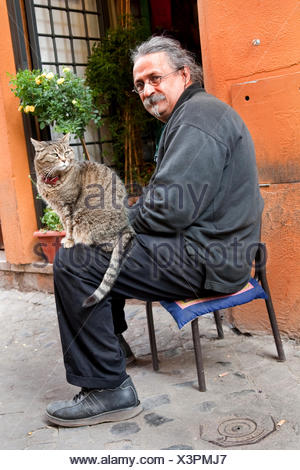 man with a cat  on his lap sitting in an alley of Trastevere, Italy, Trastevere, Rome - Stock Photo