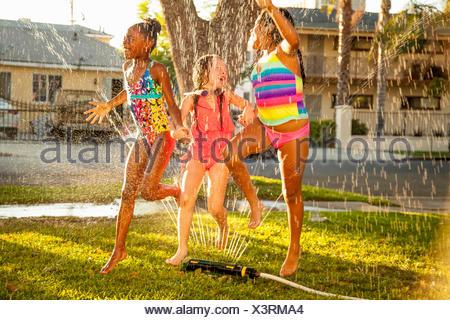 Three girls running and jumping in garden sprinkler - Stock Photo