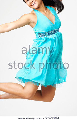 Portrait of a young woman smiling and jumping - Stock Photo