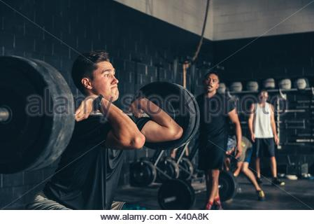 Man and trainer training with barbell in gym - Stock Photo