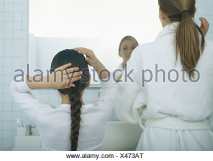 Woman and girl fixing hair, rear view - Stock Photo