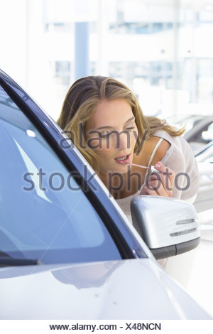 Woman applying lip gloss in side-view mirror of car in car dealership showroom - Stock Photo