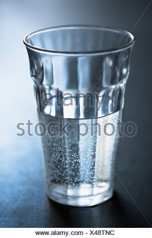 Air bubbles in glass of water - Stock Photo