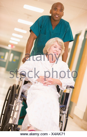 Hospital Staff Pushing Man In Wheelchair Blurred Motion Stock Photo