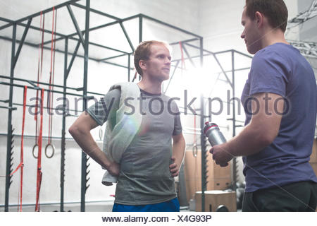 Male friends talking in crossfit gym - Stock Photo