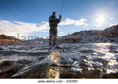 split view of fish on the line and fisherman - Stock Photo