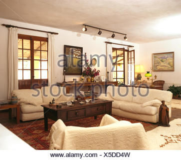 Cream Sofas And Dark Wood Coffee Table In Living Room Of Spanish Villa    Stock Photo