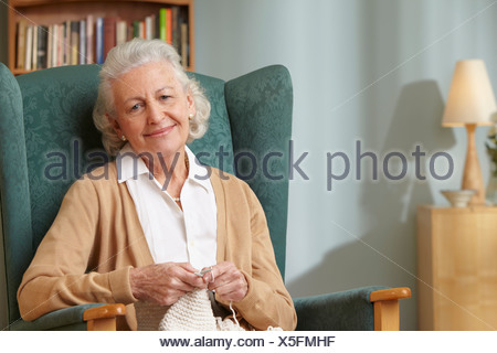 Senior woman knitting, portrait - Stock Photo