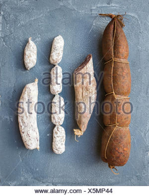 Italian salami sausages of different kinds over a rough grey-blue concrete background top view - Stock Photo