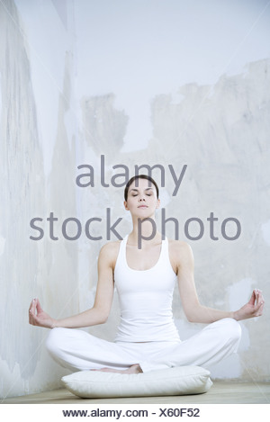 Young woman sitting in lotus position, eyes closed, full length - Stock Photo