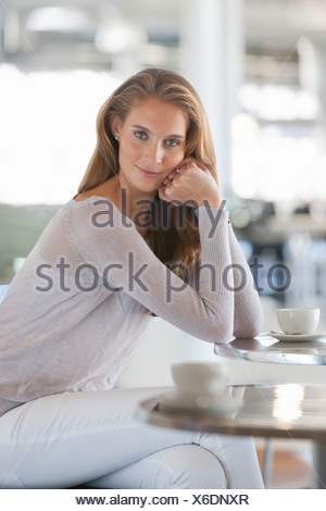 Portrait of confident woman drinking coffee at cafe table - Stock Photo