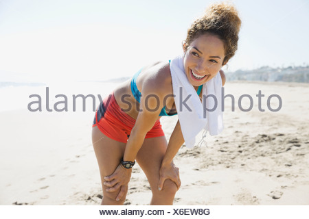 Active woman resting after workout on the beach - Stock Photo