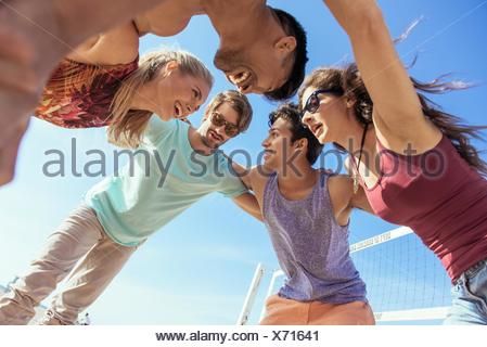 Group of friends in huddle on beach, low angle view - Stock Photo