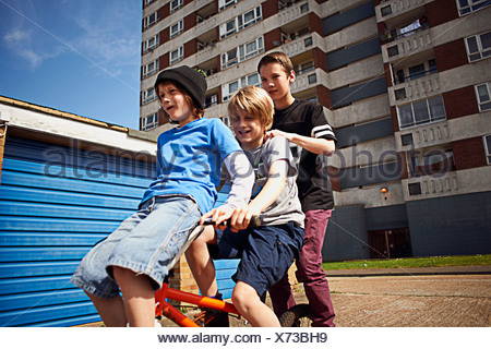 Boy giving two friends a ride on bike - Stock Photo