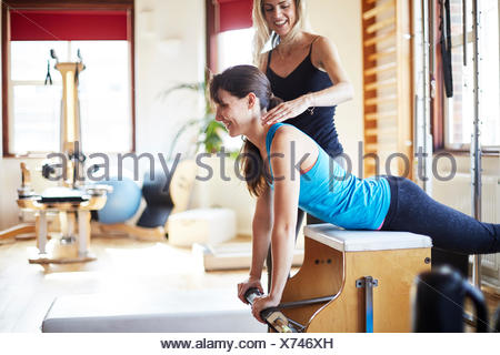 Young female student pushing up from combo chair in pilates gym - Stock Photo