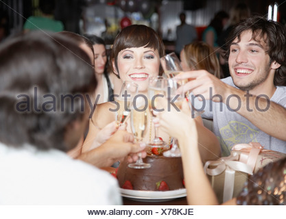 group of people toasting and smiling at a birthday party in a restaurant - Stock Photo