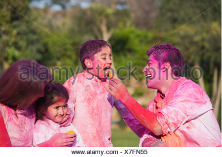 Couple celebrating Holi with their children - Stock Photo