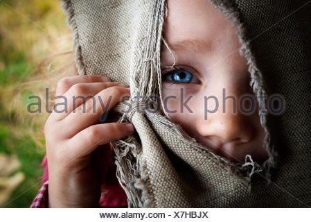 Portrait of girl (4-5) hiding face behind curtain - Stock Photo