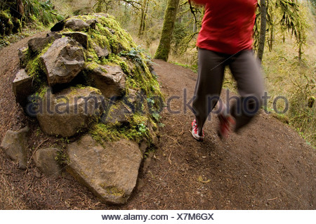 A woman running up a trail through a green, mossy forest in Silver Falls State Park, Oregon, USA. - Stock Photo