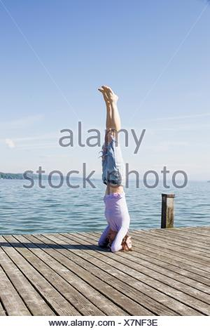 Mature woman on pier by ocean balancing on head - Stock Photo