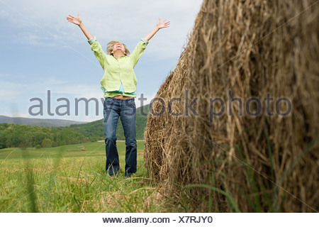 Mature woman jumping for joy in a field - Stock Photo