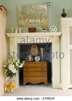 Close-up of small chest-of-drawers in white fireplace in pale green ...