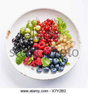 Mix of fresh berries with leaves in vintage ceramic colander on white background - Stock Photo