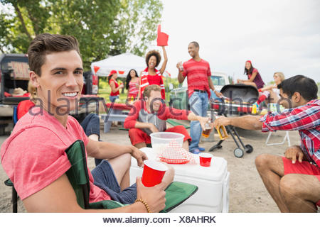 Man relaxing at tailgate barbecue in field - Stock Photo