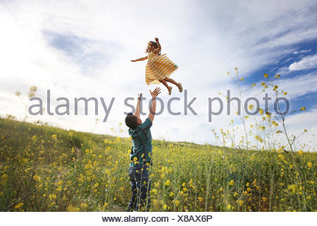 Father throwing daughter in the air - Stock Photo