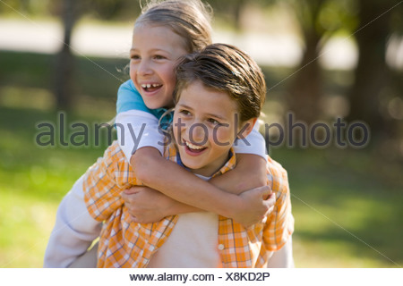 Boy giving piggyback ride to girl in park - Stock Photo