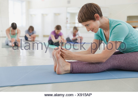 Woman instructor practicing yoga with students in yoga studio - Stock Photo